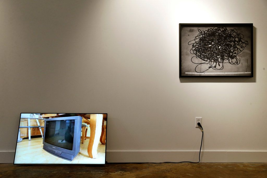 """Artist Penelope Umbrico's piece Pirouette for CRT (left), a 2012, Single channel digital video, color 5 seconds, looped Ed of 10 leans against wall next to 36"""" used Electrical Cords (eBay), 2014 Chromogenic Print in the Dallas Medianale show at The MAC gallery in Dallas May 23, 2019."""