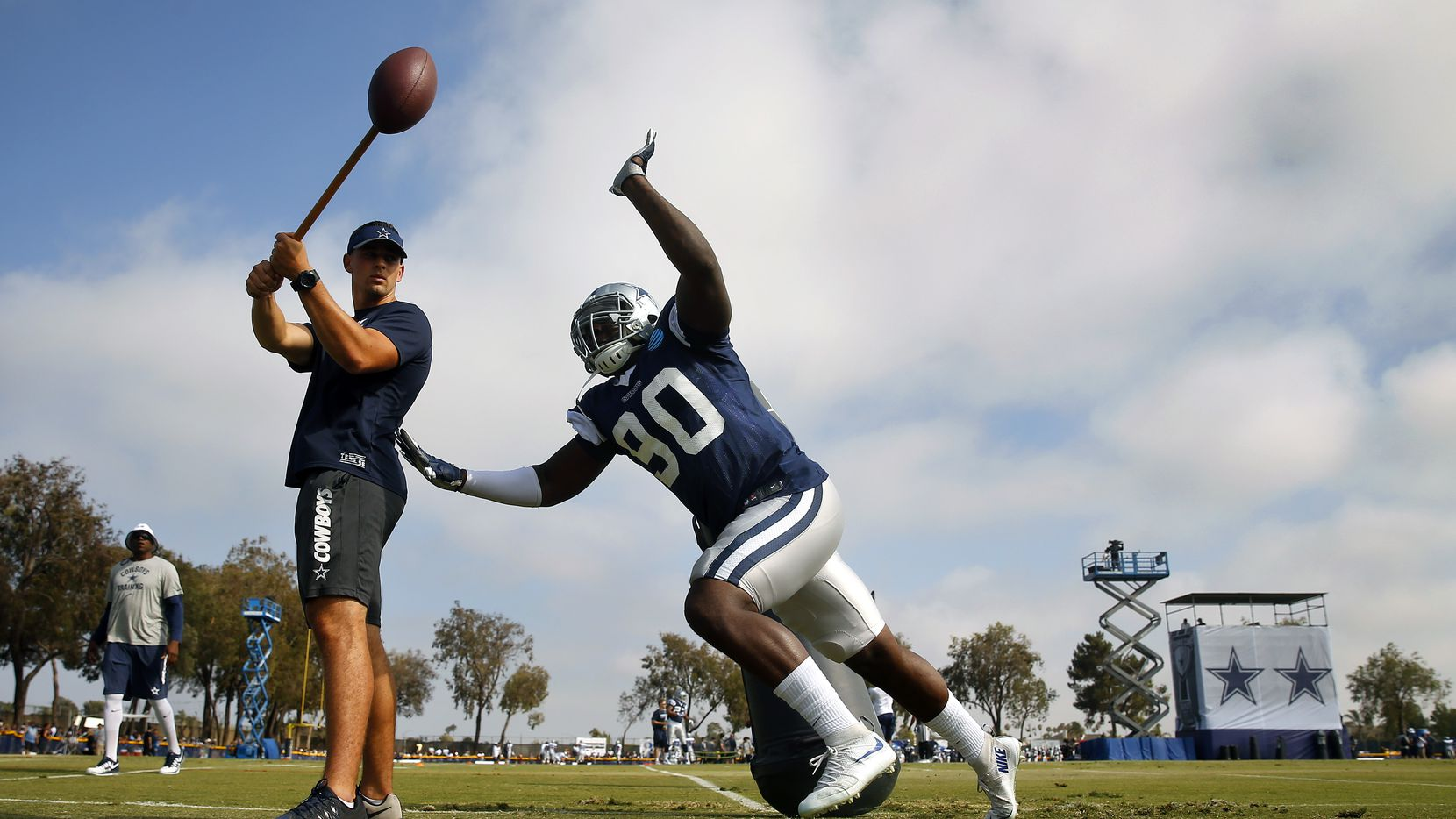 Dallas Cowboys defensive end Demarcus Lawrence (90) races in a circle to knock down the football during afternoon practice drills at training camp in Oxnard, California, Thursday, August 4, 2016. (Tom Fox/The Dallas Morning News)