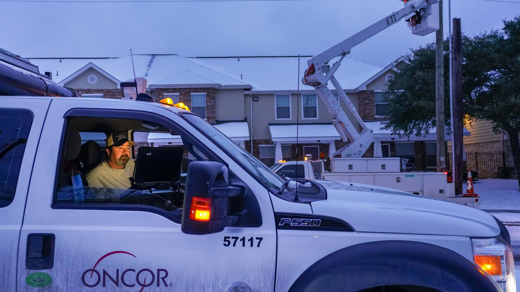 An Oncor crew works on along Elsie Faye Heggins Street as power outages continue across the state after a second winter storm brought more snow and continued freezing temperatures to North Texas on Wednesday, Feb. 17, 2021, in Dallas.