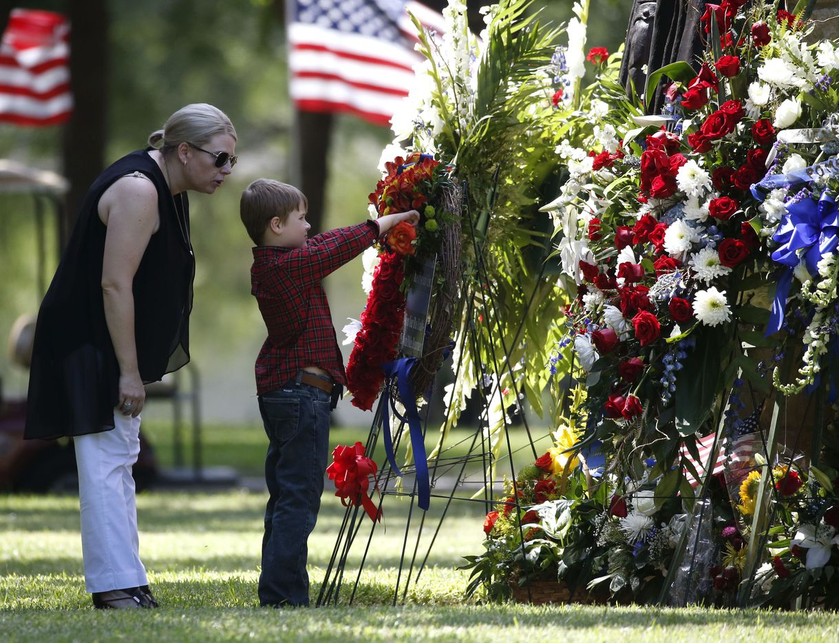 Katrina Ahrens, wife of fallen Dallas police officer Lorne Ahrens, watches her son Magnus Ahrens, 8, pick a flower to put in the grave of her husband in the Garden of Honor at Restland Funeral Home and Cemetery in Dallas on July 13, 2016. Ahrens and four other officers were gunned down during an ambush on police in downtown Dallas.