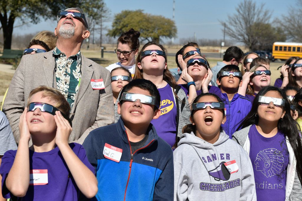 Students look directly at the sun with their eclipse glasses at UNT Discovery Park.