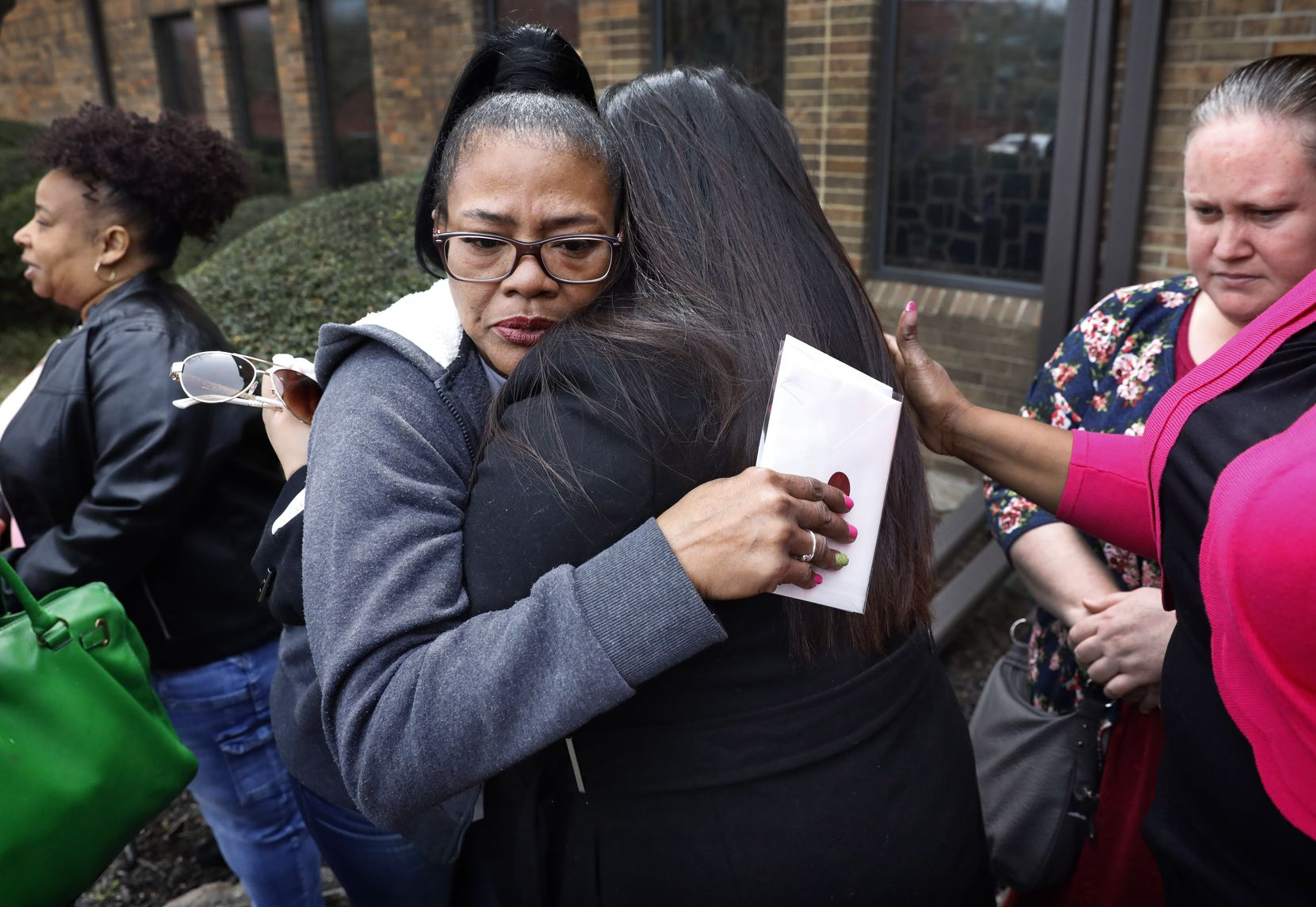 Tammy Kirk, mother of LaTiffiney Rodgers, receives hugs from friends and family after a funeral service for Rodgers on Feb. 22 in DeSoto.