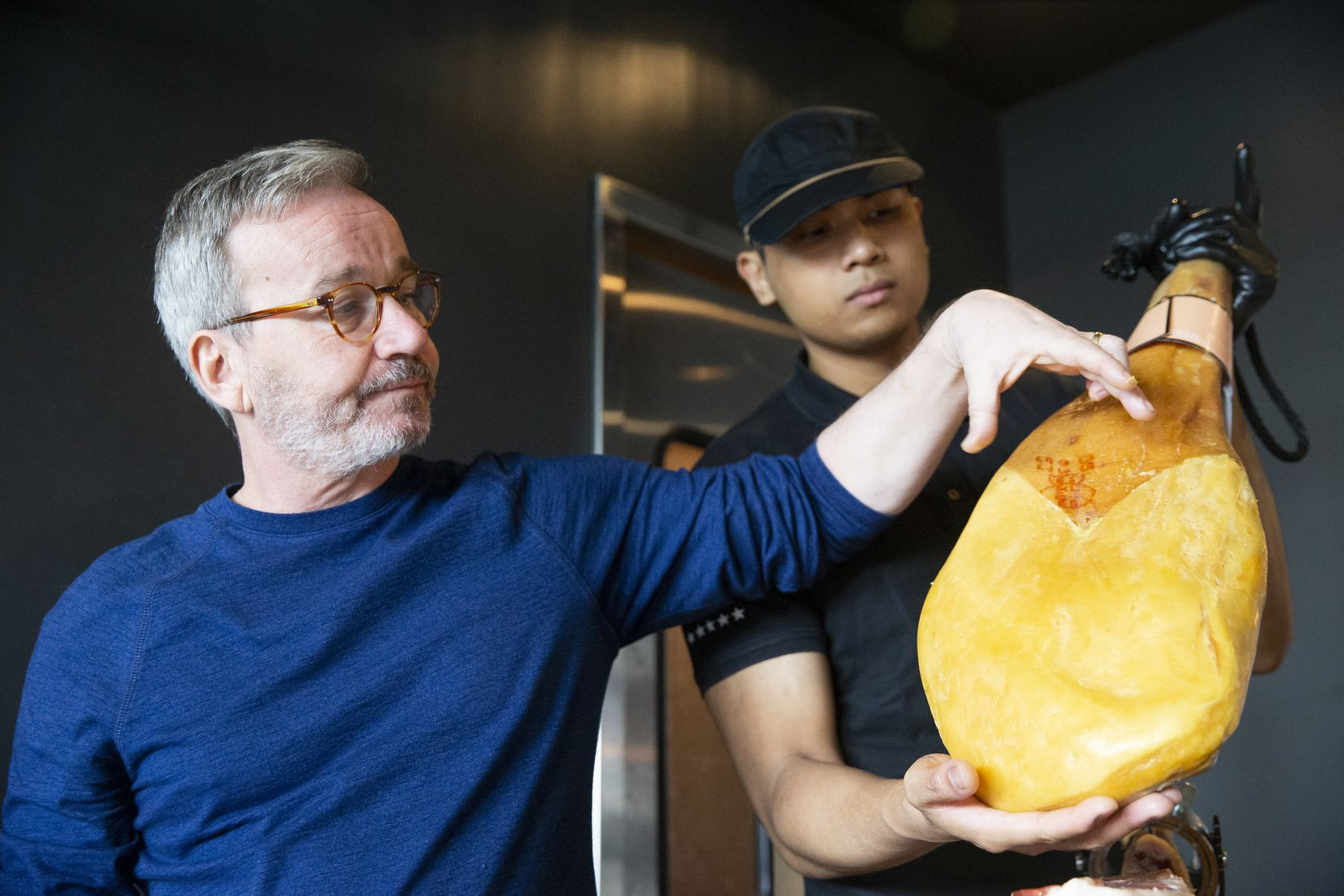 Maestro jamoneros Xavi Bru (left) and Spike Comia teach new employees about the different hams at the new jamón Ibérico shop Enrique Tomas on Feb. 10, 2020 in Dallas. (Juan Figueroa/ The Dallas Morning News)