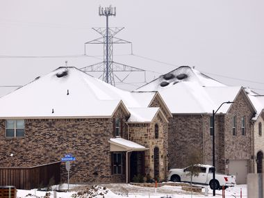 Large electrical transmission lines are pictured in a new housing development in South Arlington, Feb. 17, 2021. Rolling power outages have disrupted service to customers following the snowstorm and deep freeze. (Tom Fox/The Dallas Morning News)