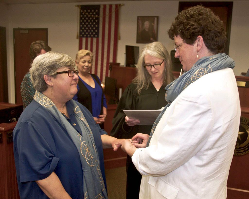 In this April 1, 2016 photo provided by John Selig, Patti Fink, left, receives a ring from Erin Moore during their wedding ceremony in Dallas, Texas. At center is Judge Tena Callahan. Same sex marriage was legalized by the U.S. Supreme Court on June 26, 2015. (John Selig via AP)