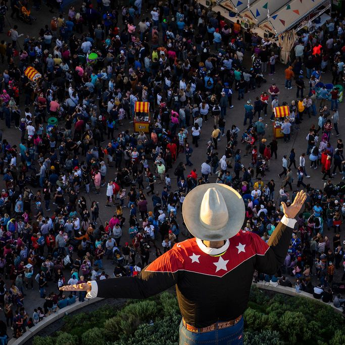 The last rays of sunlight fall over Big Tex as crowds fill the State Fair of Texas.
