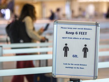 A passenger walks past a sign enforcing social distancing guidelines at Dallas Love Field airport in Dallas on Sunday, July 26, 2020.
