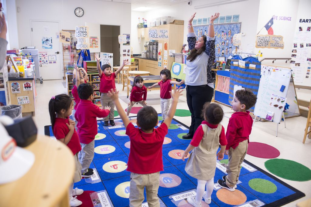 A pre-K teacher leads 3-year-old students in breathing exercises at the Momentous School.