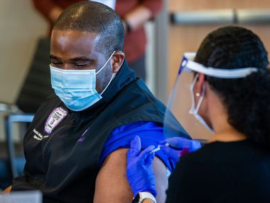 """COVID unit nurse Tonychris """"TC"""" Nnaka, (left) received a dose of the Pfizer COVID-19 vaccination from Director of Occupational Health Stephanie Collins during a media event Dec. 15 at Parkland Hospital."""