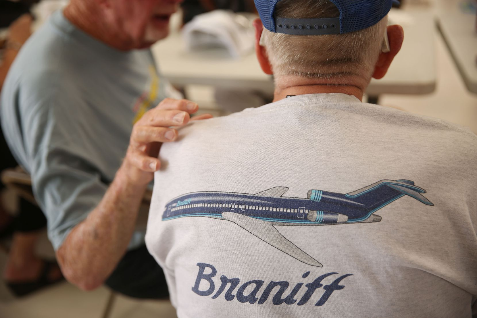 Charlie Monch (left) embraced Dale Eddy as the retired Braniff pilots visited during the 41st annual Braniff International Airways pilots picnic at Denton Municipal Airport on Monday.