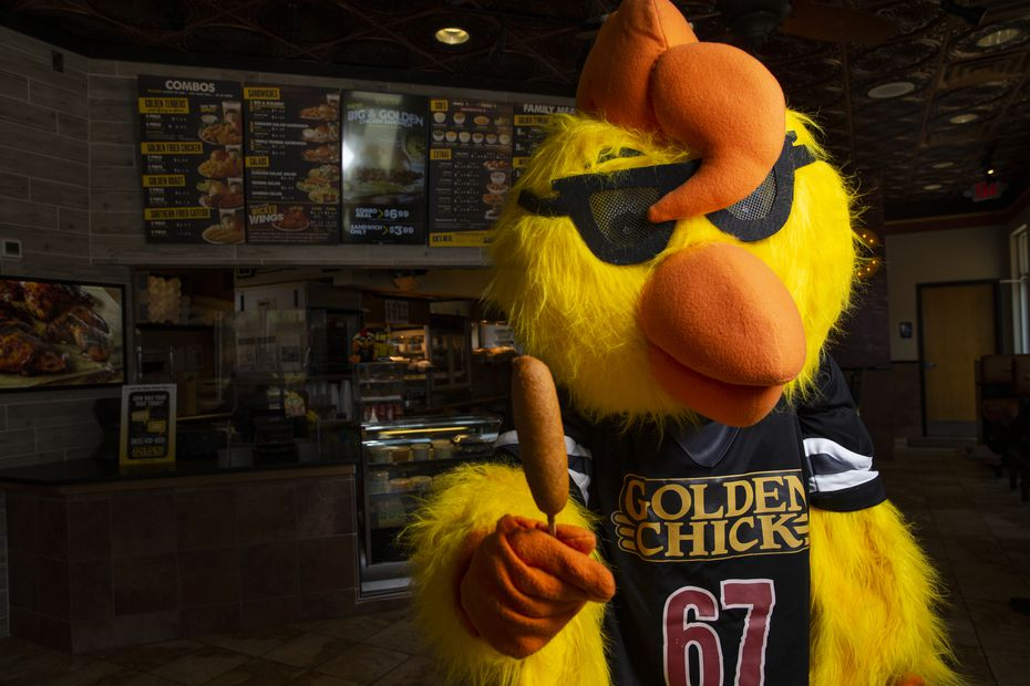 Clucky, Golden Chick's mascot, holds a Fletcher's corny dog at the fast-food restaurant at 16740 Hillcrest Road in Dallas.