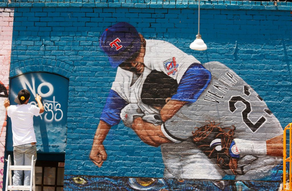 """Dallas-based muralist Isaac """"IZK"""" Davies adds the promotional lettering to his finished mural of the famous Nolan Ryan punch scene on the Crowdus St. side of Wits End in Deep Ellum. The mural was commissioned to promote DJ Edgar Blue No Request Served Sunday's roof top party at Wits End. (Ron Baselice/The Dallas Morning News)"""
