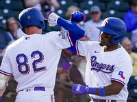 FILE - Rangers infielder Andy Ibanez celebrates with first baseman Josh Altmann after hitting a 3-run home run during the eighth inning of a spring training game against the Chicago Cubs at Surprise Stadium on Thursday, Feb. 27, 2020, in Surprise, Ariz.