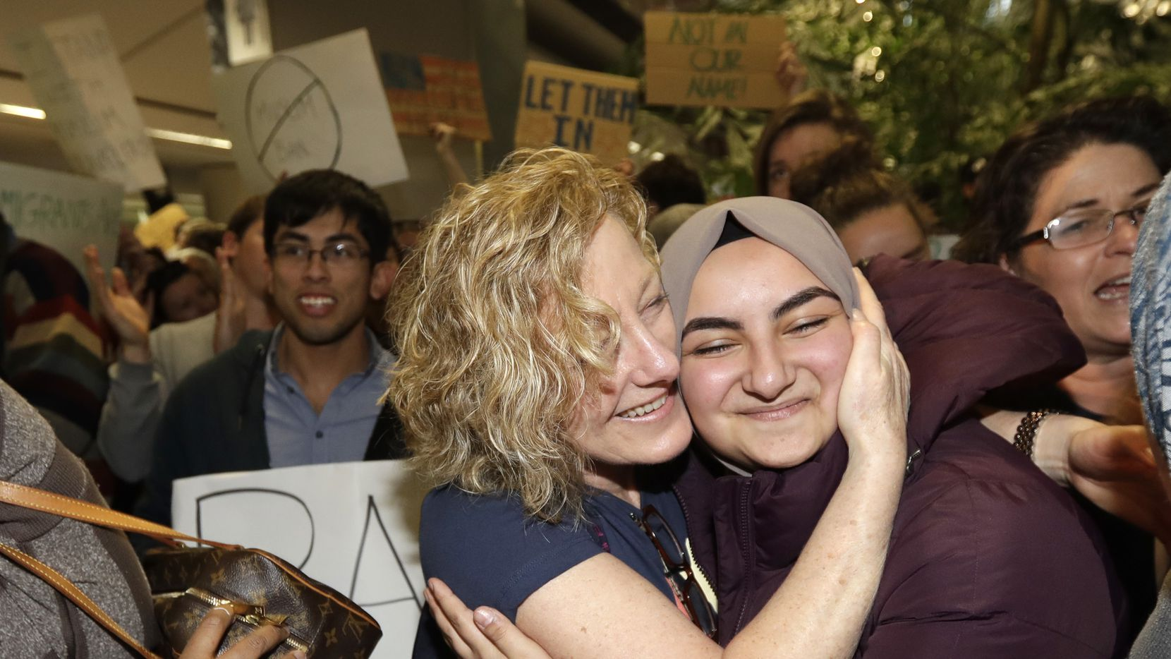 Demonstrators embrace in front of the arrivals terminal at San Francisco International Airport during demonstrations against President Donald Trump's executive order that bars citizens of seven predominantly Muslim countries from entering the U.S. Saturday, Jan. 28, 2017, in San Francisco.
