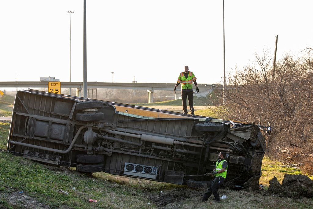 A workers attempt to turn a school bus from Bishop Dunne Catholic School that overturned in the westbound lanes of I-30 near Loop 12 in Dallas on Thursday, Jan. 17, 2019. Multiple people on board the bus were been taken to nearby hospitals after the crash.