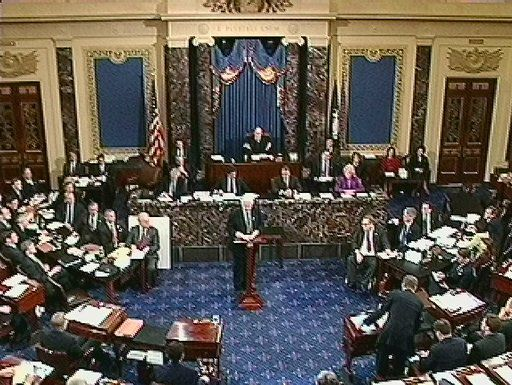 Lead prosecutor Rep. Henry Hyde, R-Ill., shown in this video image, makes his opening statement during the impeachment trial of President Bill Clinton on the Senate floor in the Capitol, Thursday, Jan. 14, 1999, in Washington. The two tables on either side of the podium were added for the impeachment proceeding. At right are the attorneys for Clinton; at left is the prosecution.