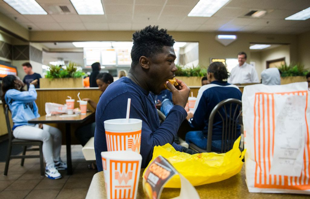 Lone Star High School football player Darrin Smith, 16, takes a bite of his triple burger with fries as he and his classmates celebrate their district football title at Whataburger in Frisco.