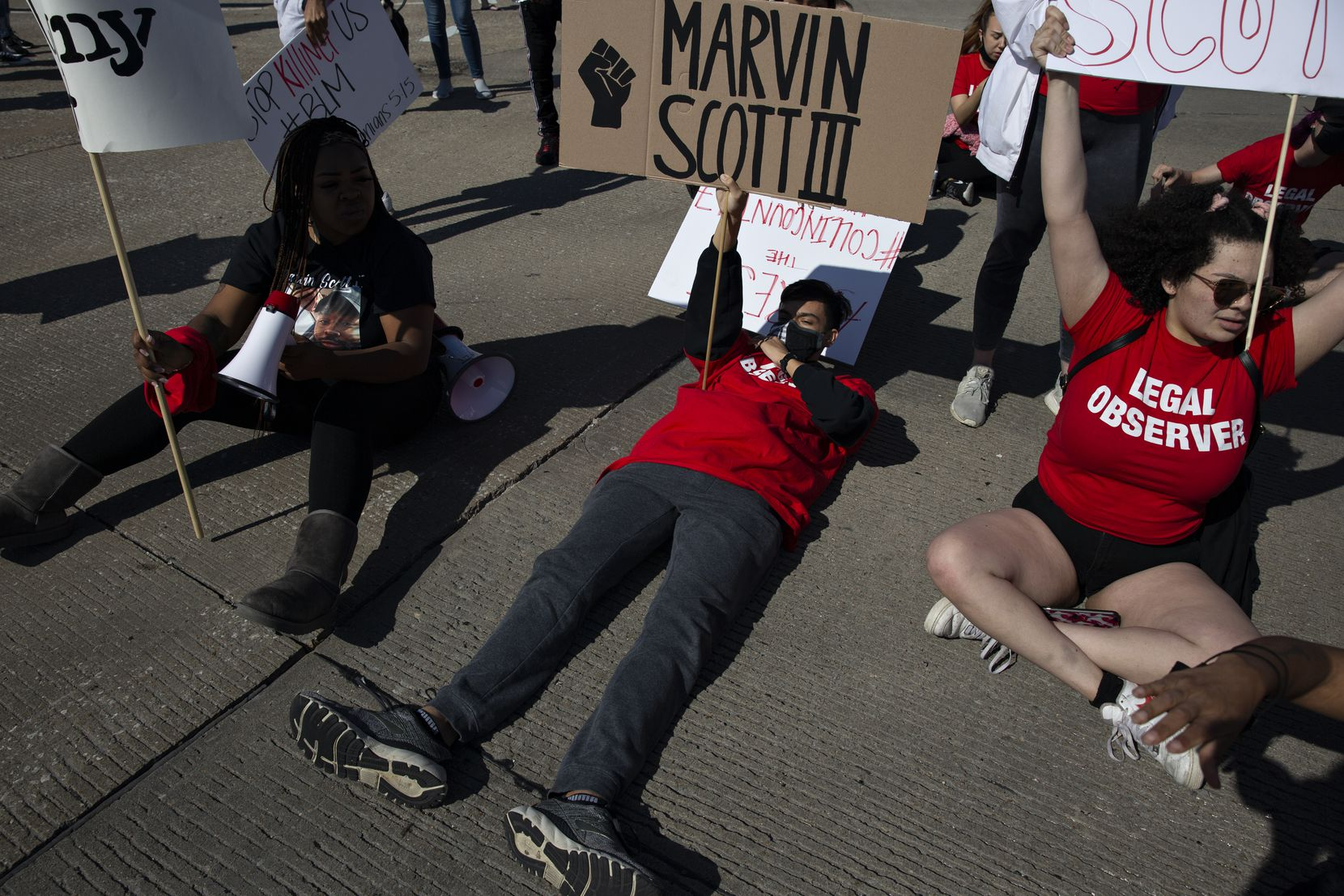 Michael Chyobotov (center) lays on the street as he occupies an intersection along with other demonstrators during a march outside of the Allen Outlets on Sunday, March 21, 2021. They demanded justice for Marvin Scott III, who died a week prior while in custody at the Collin County Jail on March 14, 2021. (Shelby Tauber/Special Contributor)