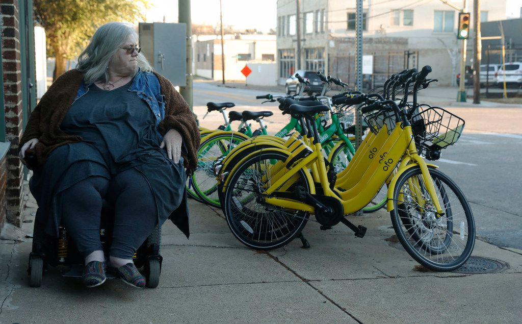 Melody Townsel, who teaches AP English at Booker T. Washington High School for the Performing and Visual Arts, maneuvers her wheelchair past rental bikes on Akard Street in downtown Dallas on Jan. 8, 2018. She uses public railway transit to get to work and often finds bikes and their riders to be problematic.