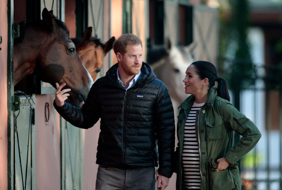 Britain's Prince Harry and Meghan Markle, duchess of Sussex, walk together during a visit to the Moroccan Royal Equestrian Sports Complex in Rabat, Morocco, in February.