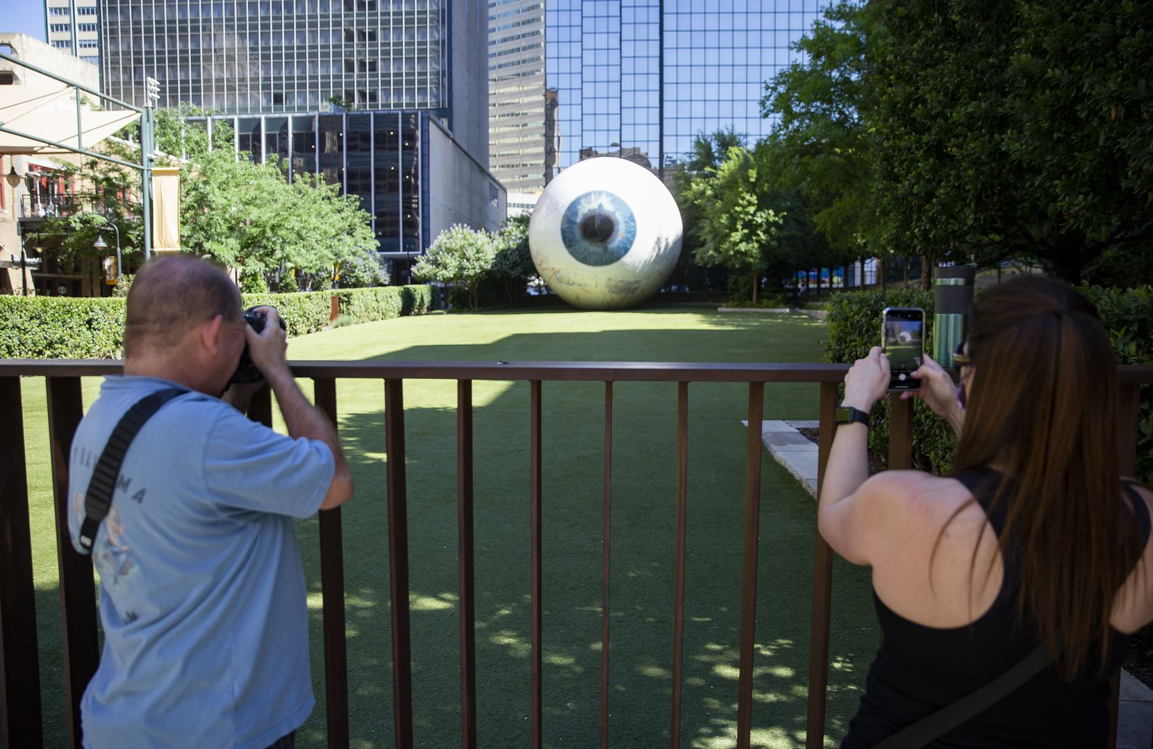 People take photos of the 'Eye' sculpture with graffiti covered up on Saturday morning, May 30. Protesters defaced it during Friday night's protest demonstration.