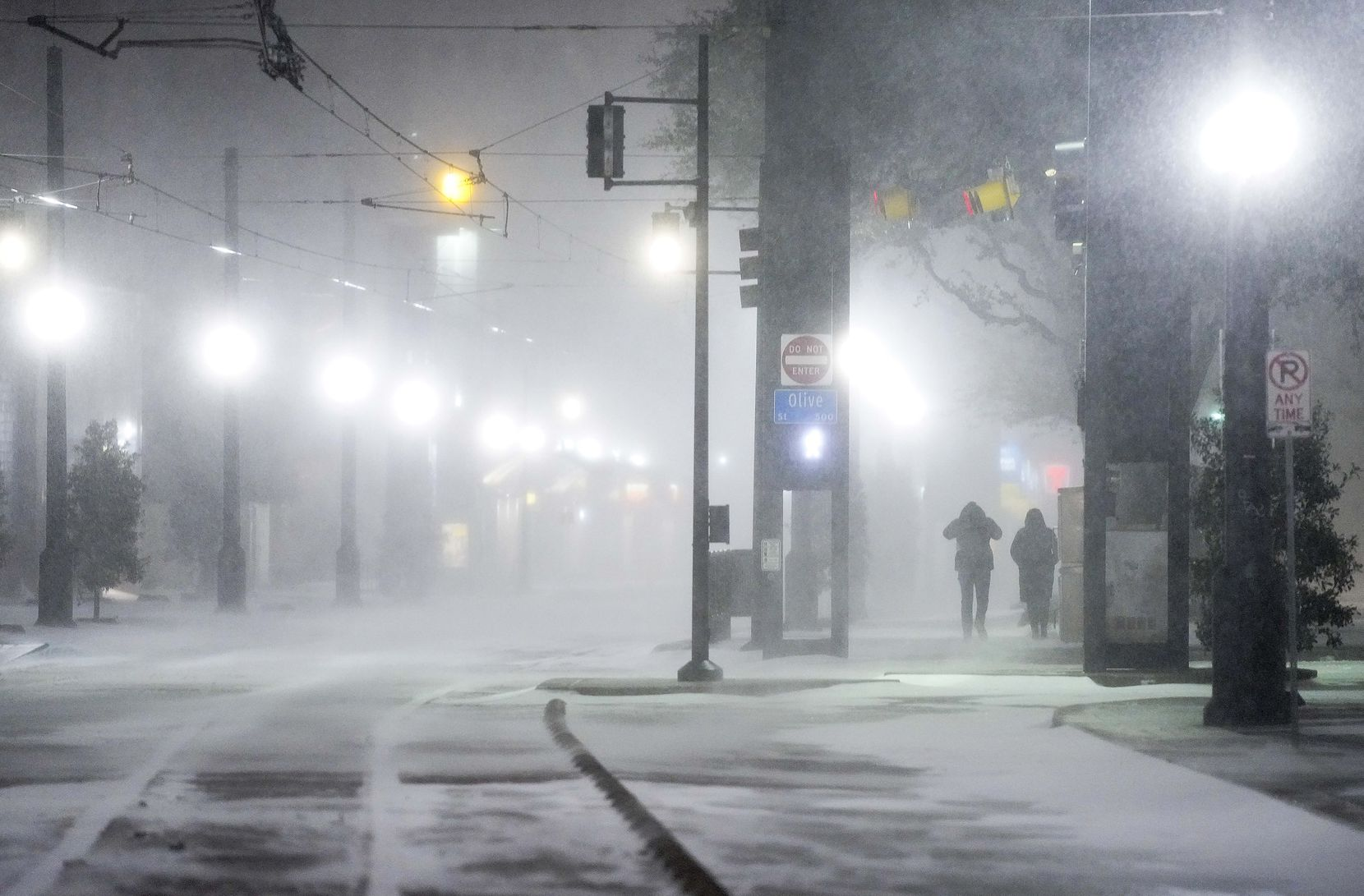 Blowing snow obscures people walking along Bryan Streen near the Pearl/Arts District station as a winter storm brings snow and freezing temperatures to North Texas on Sunday, Feb. 14, 2021, in Dallas.