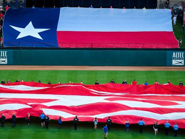 First responders from the Arlington police and fire departments unfurl large US and Texas flags at Globe Life Park before a game between the Texas Rangers and the Tampa Bay Rays on Wednesday, Sept. 11, 2019, in Arlington.