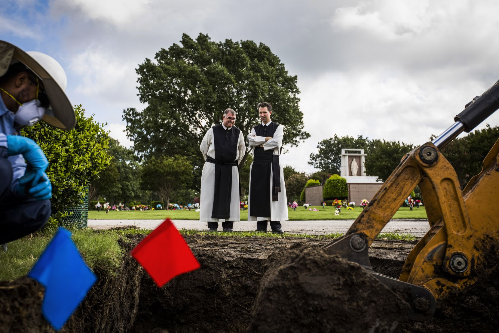 The Rev. Paul McCormick (left) and the Rev. Joseph Van House watch as workers prepare to remove the remains of two fellow Cistercian monks from their graves at Calvary Hill Cemetery in Dallas.