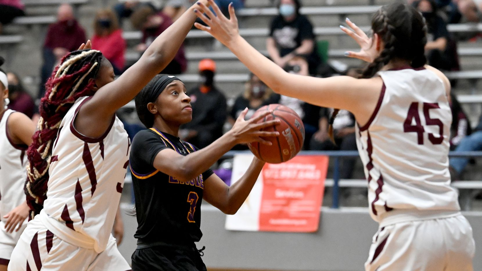 Richardson's Zariah Tillman drives to the basket between Plano's Sanaa Murphy-Showers and Avery Foltz (45) in the second half of Monday's Class 6A area-round playoff game. Plano won 57-46. (Matt Strasen/Special Contributor)
