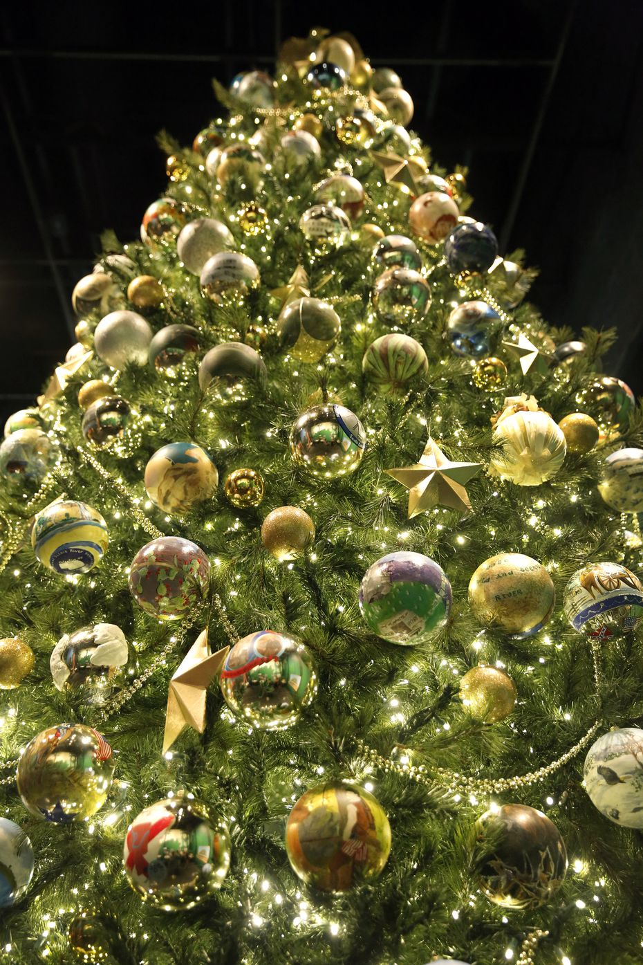 """An 18-foot replica of the official White House Blue Room Christmas tree is covered with gold stars, gold beaded garland, and hundreds of gold ball ornaments — each depicting a different park or historic site. The tree is part of the """"Holiday in the National Parks"""" exhibit at the George W. Bush Presidential Center."""