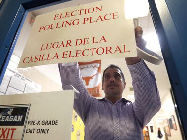 Dallas County election worker Maxx Nunez tapes up a sign before polls open for Super Tuesday voting at John H. Reagan Elementary School in the Oak Cliff section of Dallas, Tuesday, March 3, 2020.