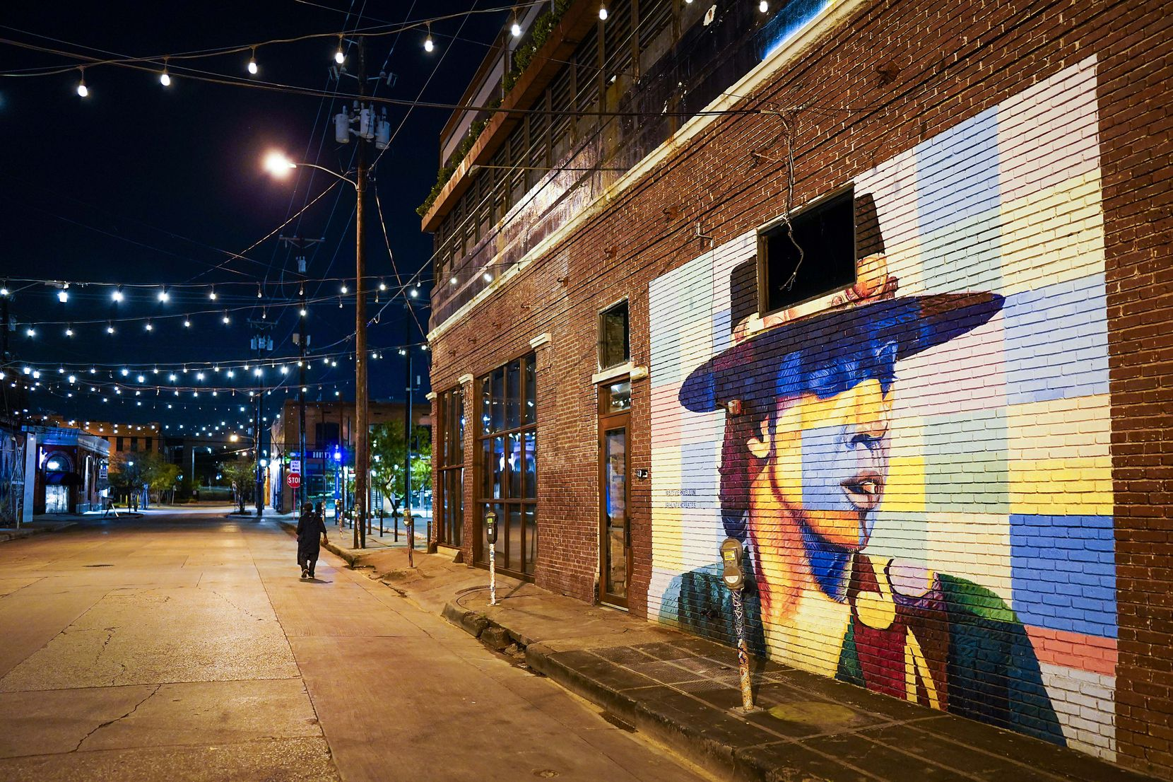 Crowdus Street in Deep Ellum sits empty except for one pedestrian at around 9:00 p.m. on  the normal crowded Saturday night on March 28, 2020, in Dallas.