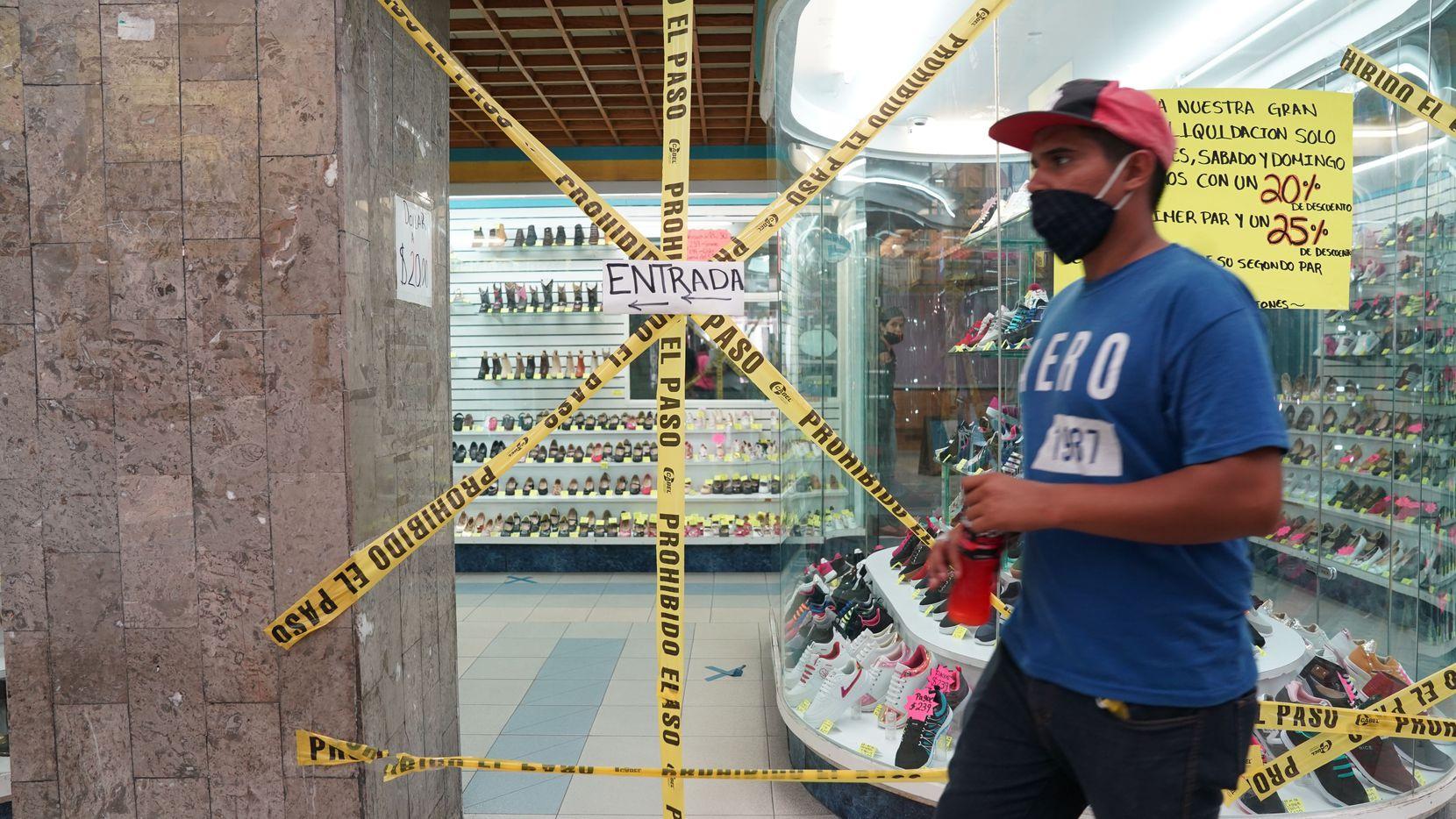 Una persona camina frente a una zapatería cerrada en la Ciudad de México como una medida de contención a covid-19.