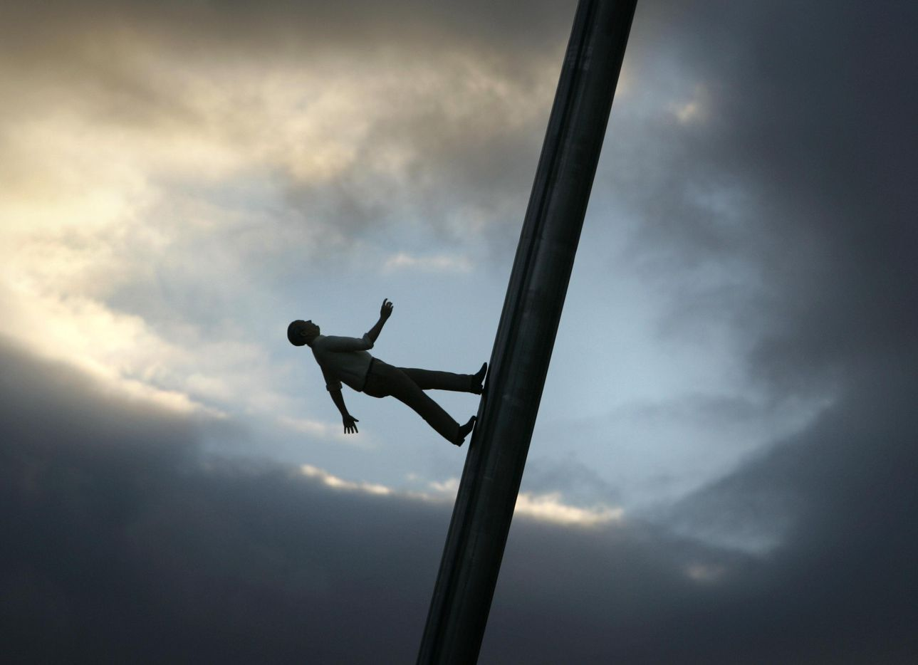 """An early evening cloud formation provided a dramatic background for one of the six life-size human figures on the Jonathan Borofsky sculpture named """"Walking to the Sky"""" at the Nasher Sculpture Center on the evening of March 22, 2005, in Dallas. The 100-foot-tall sculpture, which has been on display at Rockefeller Center in New York, was on display at the Nasher Sculpture Center for the following year."""