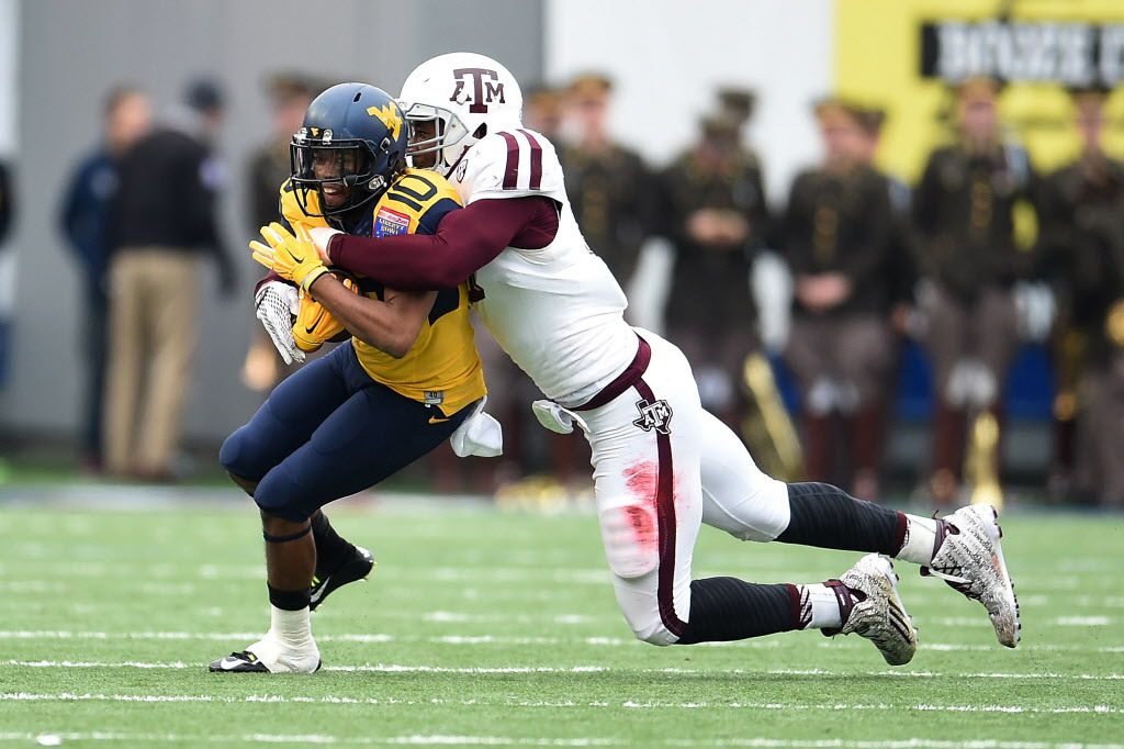 MEMPHIS, TN - DECEMBER 29: Jordan Thompson #10 of the West Virginia Mountaineers is brought down by Myles Garrett #15 of the Texas A&M Aggies during the second quarter of the 56th annual Autozone Liberty Bowl at Liberty Bowl Memorial Stadium on Decem