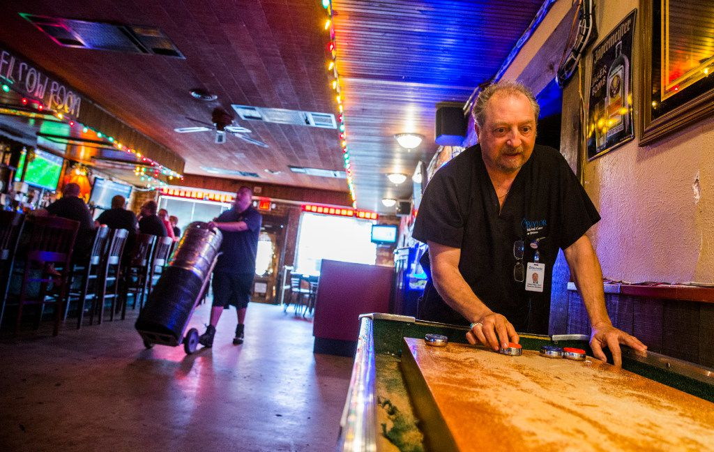 Owner Joe Nagy, right, plays shuffle board as Chris Dorough of Andrews Distributing Company brings in kegs at The Elbow Room. (Ashley Landis/The Dallas Morning News)