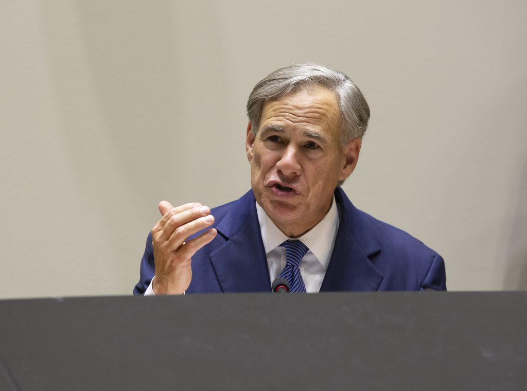 """Gov. Greg Abbott, shown at a June press conference on protest violencewith the mayors of Dallas and Fort Worth, is calling on Texans — and especially candidates for office — to take a public pledge that they will oppose """"defunding police departments."""""""
