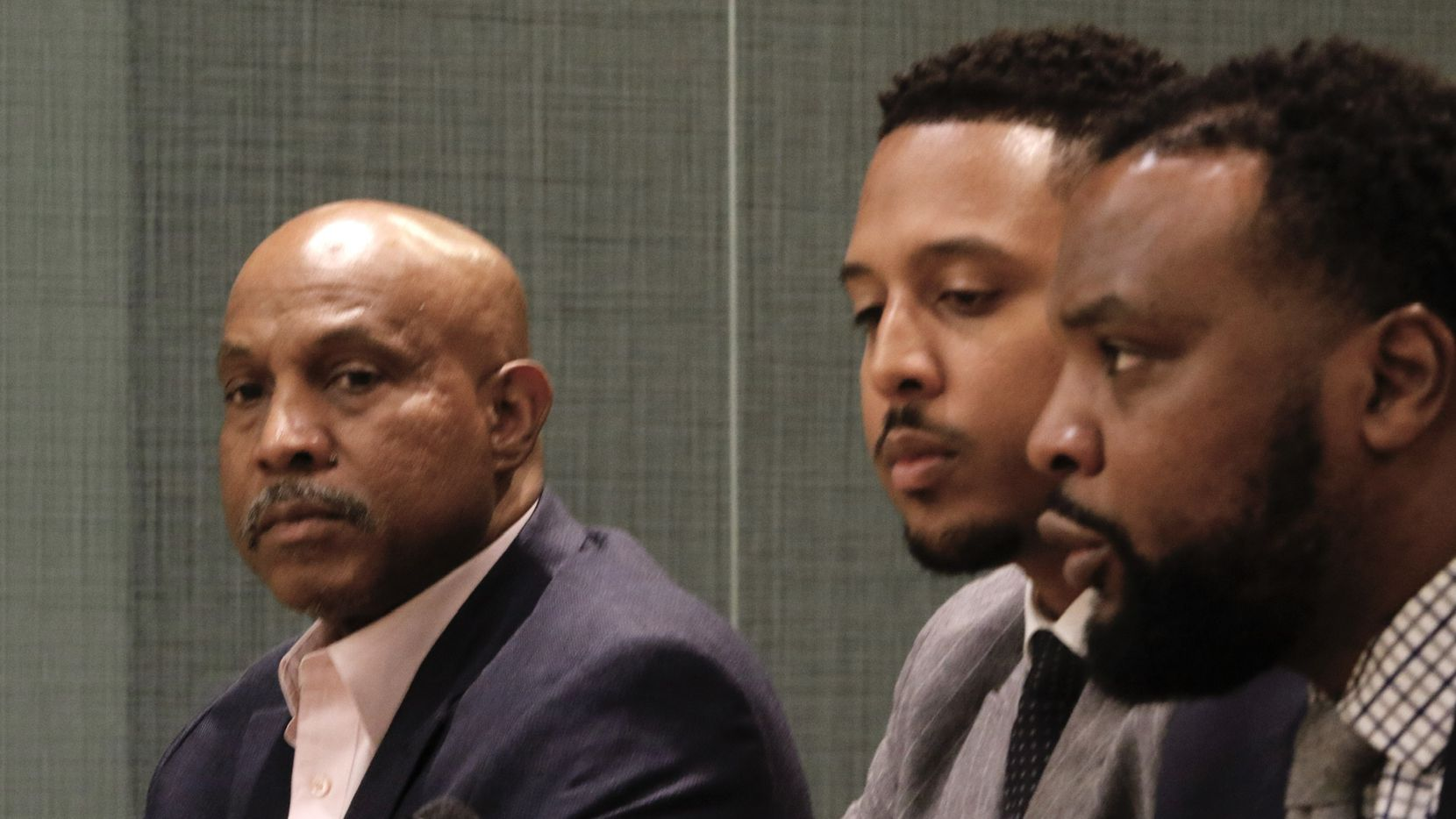 From left: Rashad Madden's father, James Madden, listens to attorneys Justin Moore and Lee Merritt during a news conference Thursday in downtown Dallas.