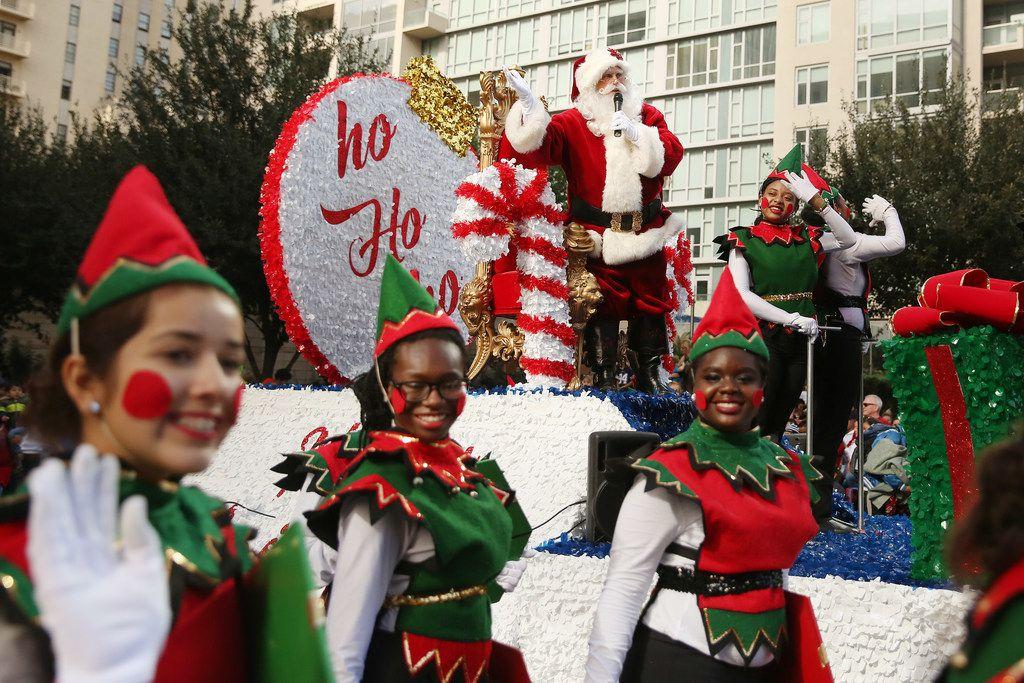 Santa Claus greets the crowd during the Dallas Holiday Parade through downtown Dallas .