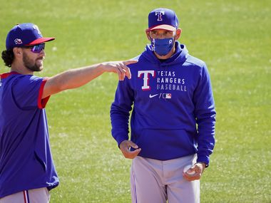 Texas Rangers infielder Charlie Culberson (left) talks with manager Chris Woodward during a spring training workout at the team's training facility on Friday, Feb. 26, 2021, in Surprise, Ariz.