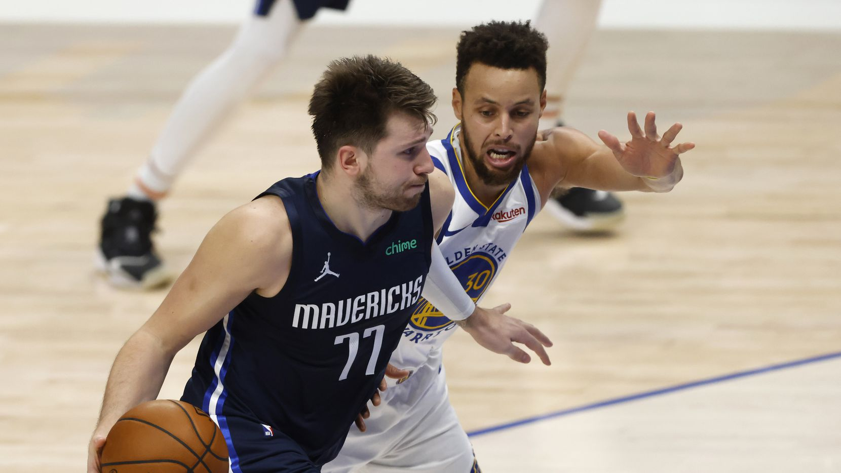 El jugador de los Mavericks de Dallas, Luka Doncic (77), conduce el balón ante la custodia del guardia de los Warriors de Golden State, Stephen Curry, el 6 de febrero de 2021 en el American Airlines Center de Dallas.