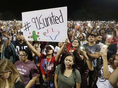 Iliani Ibarra of El Paso holds up a sign as others hold their phones during a vigil at Ponder park in El Paso, Texas on Sunday, August 4, 2019. Less than a mile away is the scene where 22 people were shot and killed and dozens more were wounded at a Walmart in El Paso.