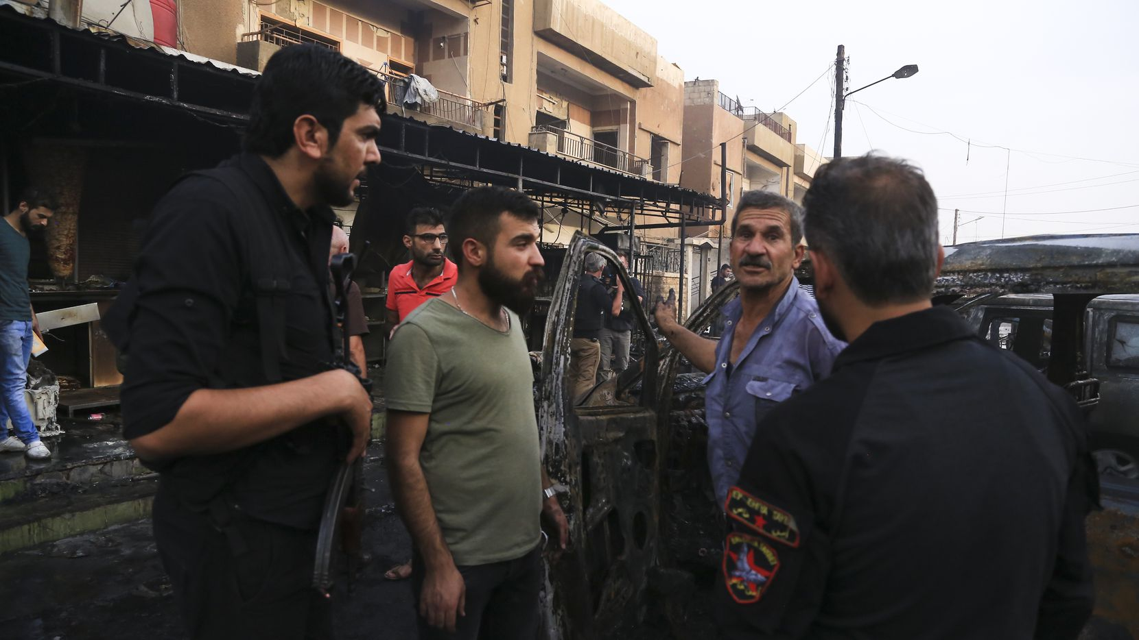 People gather after a car bomb exploded in the town of Qamishli, Syria, Friday, Oct. 11, 2019. Turkish forces faced intense resistance by U.S.-allied Syrian Kurdish fighters on the third day of Ankara's offensive, as casualties mounted, international criticism of the campaign intensified and an estimated 100,000 people fled the violence. AP Photo/Baderkhan Ahmad