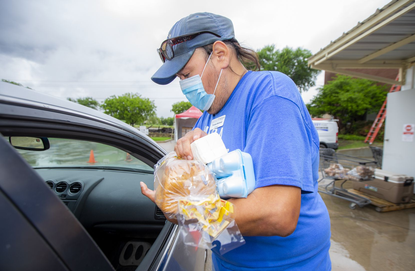 """Volunteer Trinidad Martinez loads groceries into a client's car at Metrocrest Services in Farmers Branch. Martinez, who is legally blind and has health issues, has been volunteering with various organizations since he became disabled in 2007. """"I wanted to get out there and contribute to society,"""" he says."""