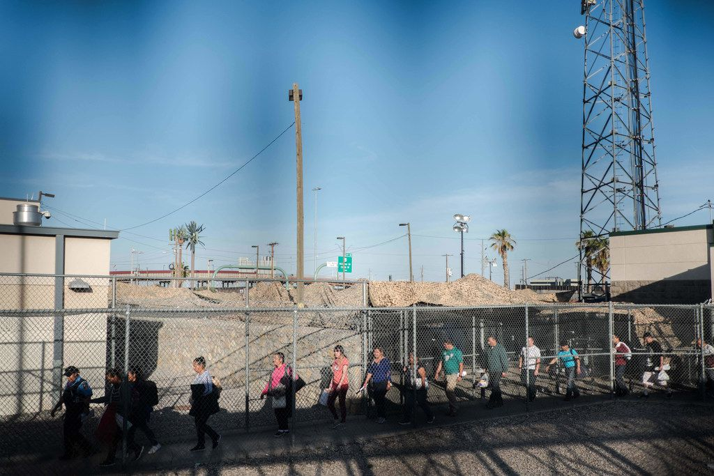 Migrants are released from an immigration holding facility nearby the Sante Fe Bridge in El Paso in June. The migrants were sent back to Ciudad Juarez to wait as they battle their court cases as part of the Trump administration's Migrant Persecution Protocols (MPP) program.