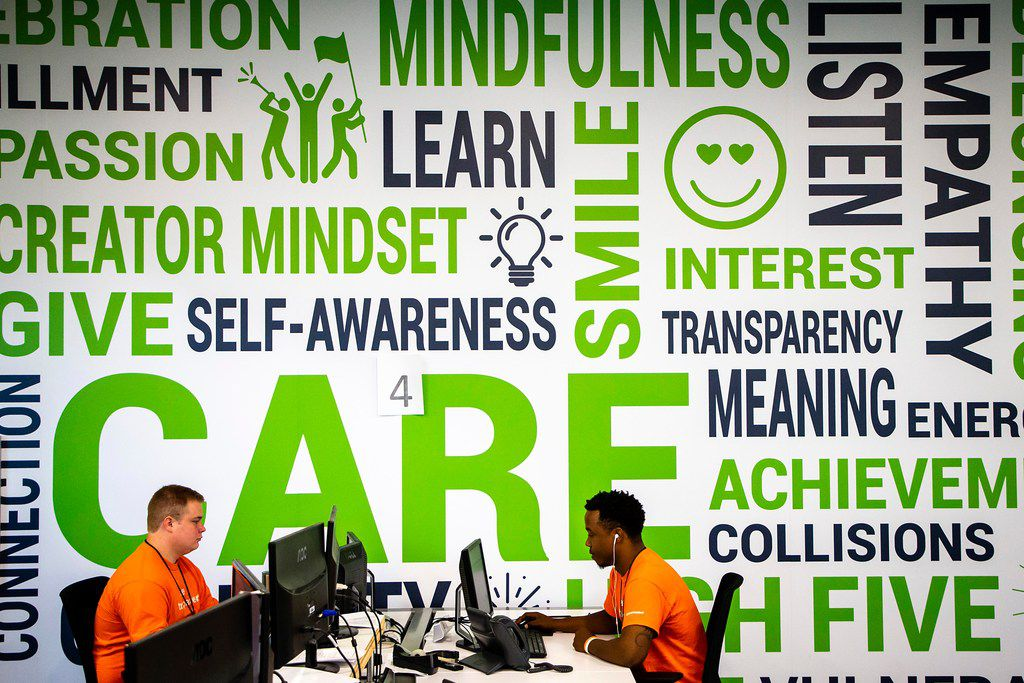 A word cloud of company values covers the wall behind Chandler Elliott (left) and Eric Brinkley at driversselect.