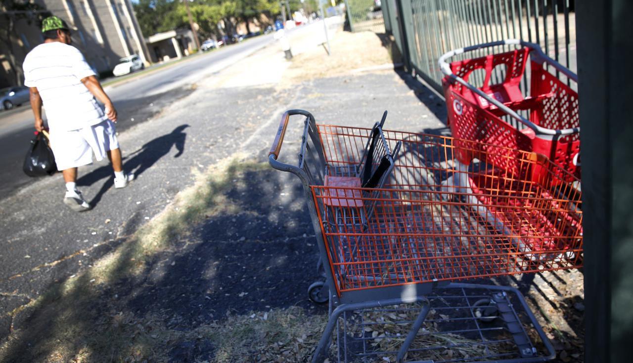 Oscar Tzab carga su mandado al pasar junto a carritos abandonados de Target y Fiesta, en Ridgecrest Road, en el vencindario de Vickery Meadow. (DMN/ROSE BACA)