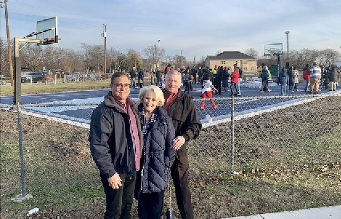 Jorge Baldor, founder of After8ToEducate, which provides transitional housing for homeless high school students, and Dianne and Jack Adleta are shown in front of the Nancy Lieberman Charities Dream Court on the Fannie C. Harris Youth Center in East Dallas. The Adletas paid for the court as part of their company's 100th anniversary,