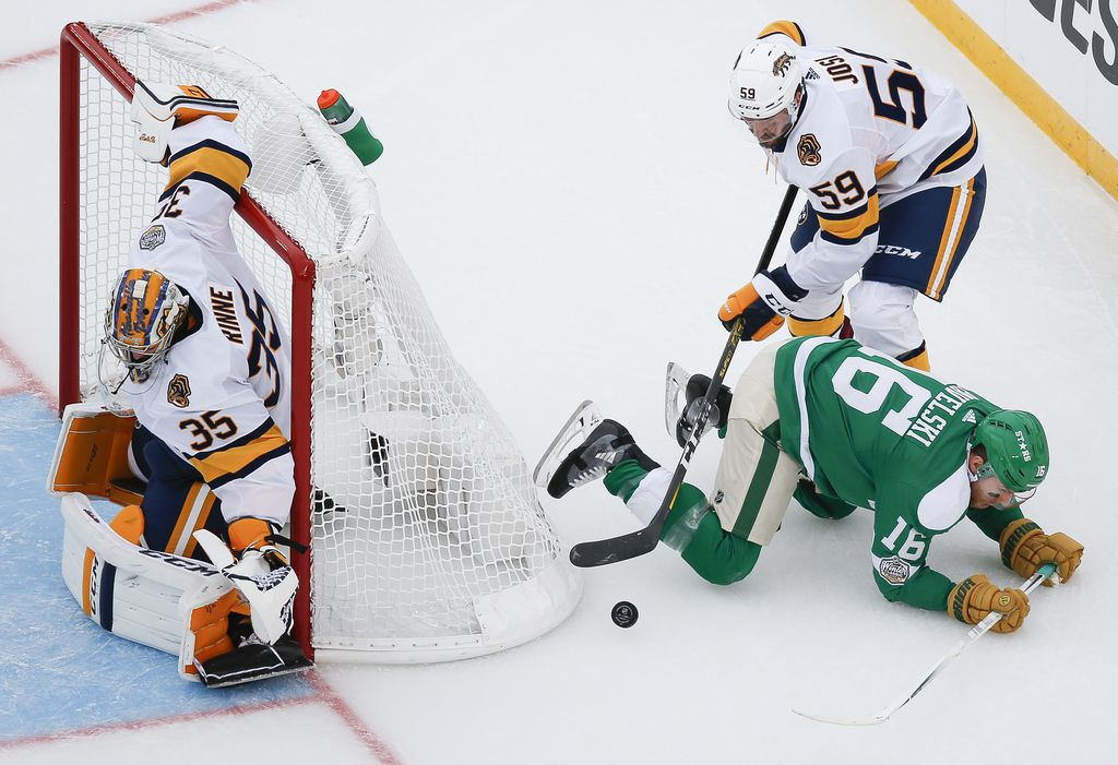 Dallas Stars center Joe Pavelski (16) is knocked down while battling for the puck with Nashville Predators defenseman Roman Josi (59) during the second period of a NHL Winter Classic matchup between the Dallas Stars and the Nashville Predators on Wednesday, January 1, 2020 at Cotton Bowl Stadium in Dallas. (Ryan Michalesko/The Dallas Morning News)