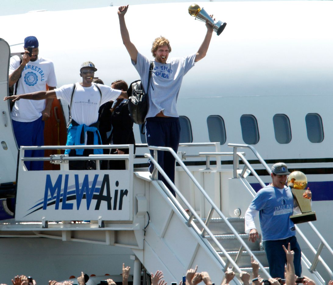 Dallas Mavericks owner Mark Cuban (lower right) held the Larry O'Brien NBA Championship Trophy, followed by the Mavs' Dirk Nowitzki holding the Bill Russell NBA Finals MVP trophy, Jason Terry doing his jet maneuver, and Tyson Chandler with his cellphone as the team arrived at Dallas Love Field to the cheers of thousands of fans on June 13, 2011. The team had defeated the Miami Heat the night before to win the NBA title.